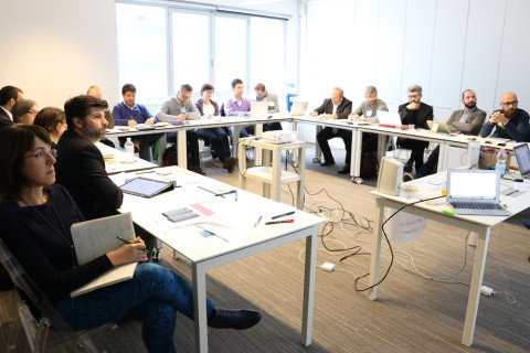 In a classroom, the Italian facilitators are sitting behind desks. The desks are arranged in a horseshoe.