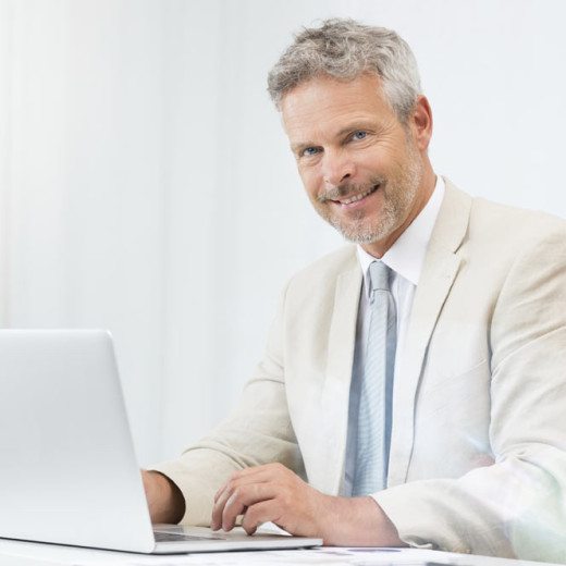Man dressed in white, sitting at desk. The man is working at the computer and smiling towards the camera