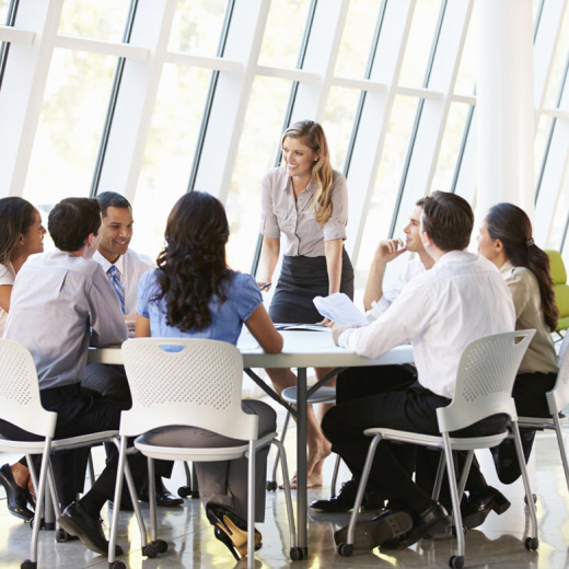 People during a meeting sitting at a table. A woman speaks up